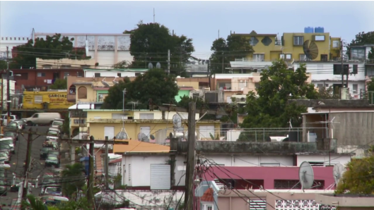"""Santurce al amanecer. El barrio pobre se caracteriza por la aglomeración y las calles estrechas. Vista fija del documental, """"La aguja"""" (2011), Oquendo Villar y Correa Vigier, dirs."""